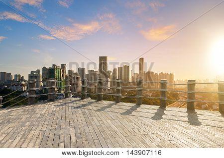 Morden city skyline and sunrise with wood floor .