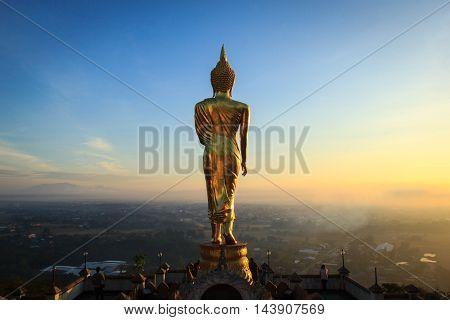 Good morning sunrise Golden buddha statue in Khao Noi temple Nan Province Thailand