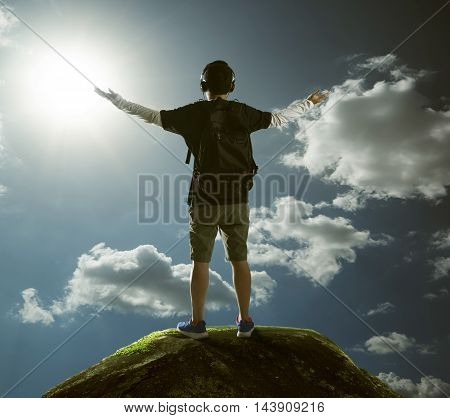Hiker with backpack standing on top of a mountain with raised hands and relaxing .