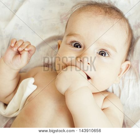 little sweet baby close up, hand in mouth smart looking, lifestyle people concept