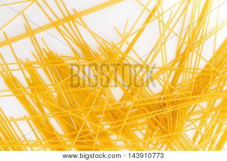 Spaghetti background. Yellow long spaghetti on white background. Thin pasta arranged in rows. Yellow italian pasta. Long spaghetti.