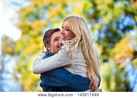 Young couple in love hugging and flirting in autumn park. Good wether in fall park for young couple in love.