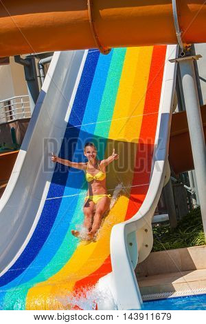 Child on water striped slide atwater park show thumb up. Water slide with flowing water in water park. Summer water park holiday. Outdoor.