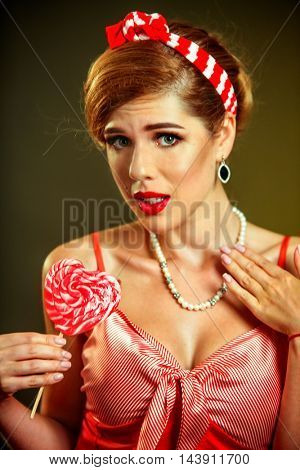 Girl in pin-up style hold striped lollipops. Pin-up retro female style. Girl pin-up style wearing red dress