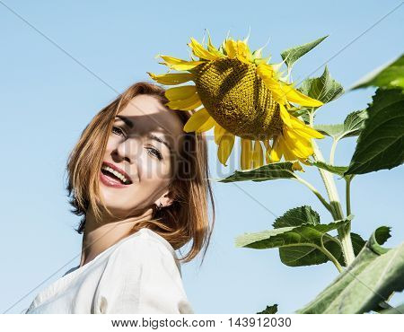 Joyful caucasian woman posing with yellow sunflower. Natural beauty. Positive emotions. Agricultural theme.