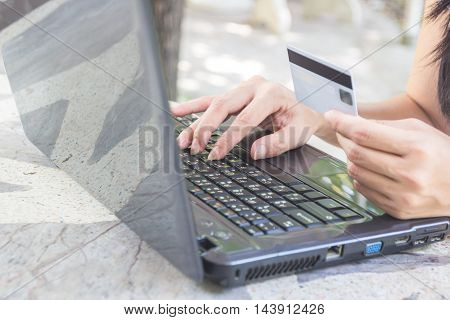 Hands holding credit card and using laptop for online shopping.
