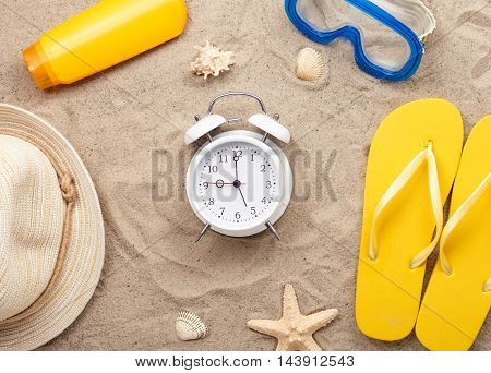 White alarm clock with beach items on sand top view. Summer background