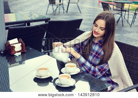 Beautiful happy girl wrapped in a blanket pours tea from a teapot into a cups in outdoor cafe