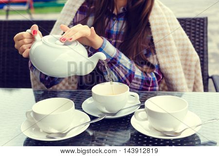 Woman hands pours tea from a teapot into a cups in outdoor cafe