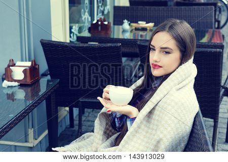 Beautiful young woman wrapped in a blanket holding a cup of tea in outdoor cafe