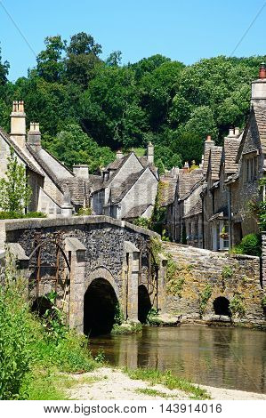 Stone bridge over the river Bybrook with cottages to the rear Castle Combe Wiltshire England UK Western Europe.