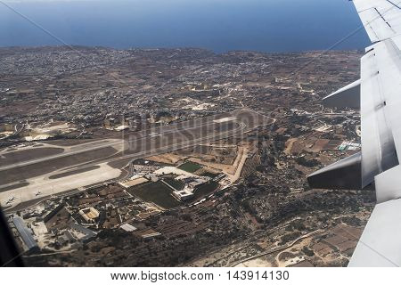 Malta airport runway and island aerial view taken inside departing aircraft.  The airport is located 5 km away from the capital Valletta.