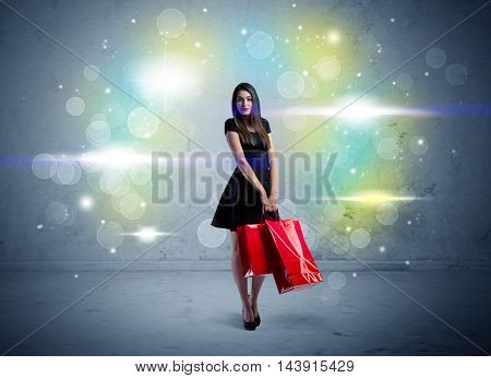 A beautiful young girl standing with long hair and red shopping bags in front of colorful light bokeh urban wall background concept