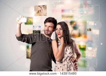 Collecting memories concept with photos in backbround and a happy young couple in love taking selfie with a mobile phone