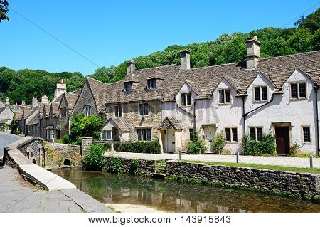 Stone cottages alongside the river Bybrook Castle Combe Wiltshire England UK Western Europe.