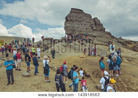 Bucegi Mountains Romania - August 6 2016: Tourists enjoy the performance of four Romanian women in colorful traditional costumes playing the tulnic near the Sphinx megalith in Bucegi mountains.