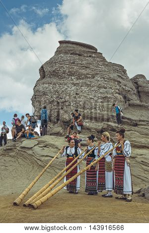 Bucegi Mountains Romania - August 6 2016: Group of young Romanian female artists wearing colorful traditional costumes play the tulnic near the legendary Sphinx megalith in Bucegi mountains.
