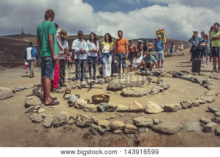 Bucegi Mountains Romania - August 6 2016: People attend a spiritual ritual organized around a spiral of stones near the Sphinx the sacred megalith located at 2216 m altitude in Bucegi Mountains.