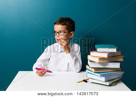 Pensive cute boy with glasses sitting at a table blue background