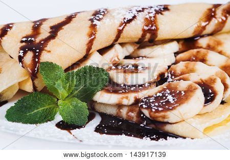 Pancakes stuffed bananas and chocolate on a plate