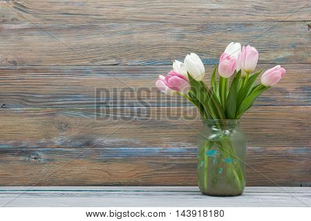 Beautiful pink flowers tulips on wooden table. Top view with copy space.