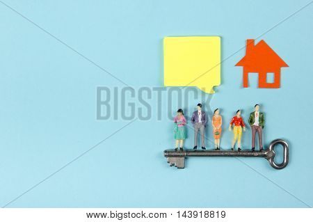 Real Estate concept. Construction building. Blank speech bubbles, people toy figures, paper model house, blueprints with key on blue architect desk table background. Top view. Copy space for ad text