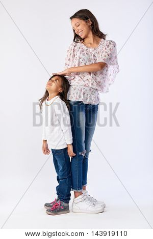 portrait of two adorable mixed race sisters measuring height difference