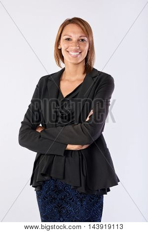 Full length portrait of mixed race business woman smiling in studio isolated on grey