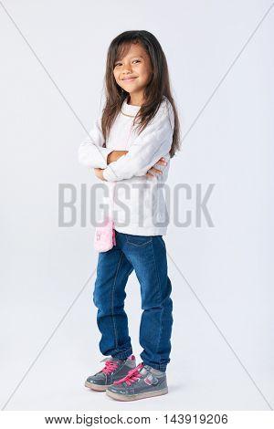 cute adorable girl posing for picture with arms crossed isolated in studio