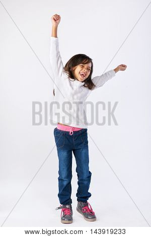 young girl celebrating with arms up and jumping isolated on white background