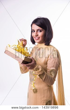 Closeup portrait of young happy excited indian woman opening ribbon of gift box, very pleased and grateful with what she received, isolated on white background. Positive emotion