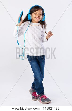 young girl playing her favorite song on headphones isolated in studio