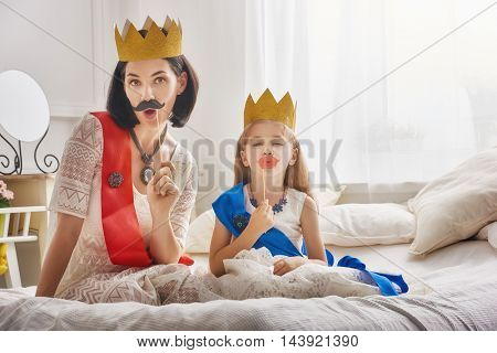 Funny family is preparing for a costume party. Mother and her child daughter girl with a paper accessories. Beautiful queen and princess in gold crowns playing together.