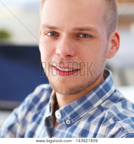 Young businessman working in office, sitting at desk, isolated