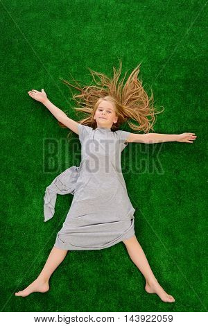 Joyful little girl lying on the grass with her arms outstretched to the sides. Kid's fashion. Summer holidays.