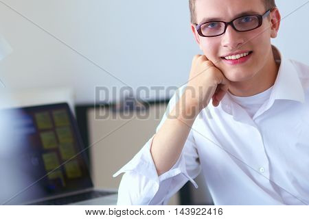 Young businessman working in office, sitting at desk