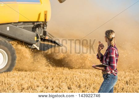 Female farmer and Combine harvester in summer with sun