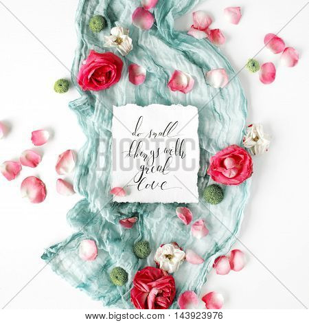 inspirational quote written in calligraphy style on paper with dry white tulips eucalyptus petals and pink textile on white background. Flat lay top view
