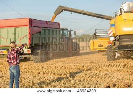 female farmer and combine harvester in wheat fields