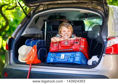 Adorable little kid boy sitting in car trunk just before leaving for summer vacation with his parents. Happy child with suitcases and toys going on journey.