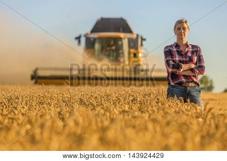 female farmer and combine harvester in her wheat fields