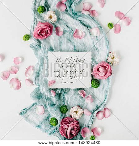 inspirational quote written in calligraphy style on paper with red roses pink petals and blue textile on white background. Flat lay top view