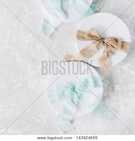 white gift cardboard boxes with brown and blue bow on concrete background. flat lat top view