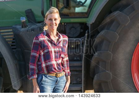 Female farmer and her big tractor with sun