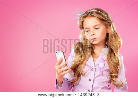 Pretty little girl with beautiful blonde hair making selfie over pink background. Little princess with a crown on her head. Kids fashion.