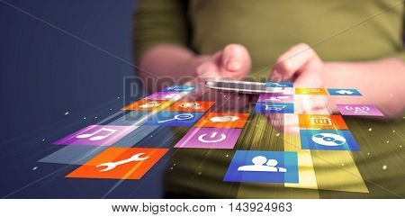 Woman holding smart phone with colorful application icons coming out