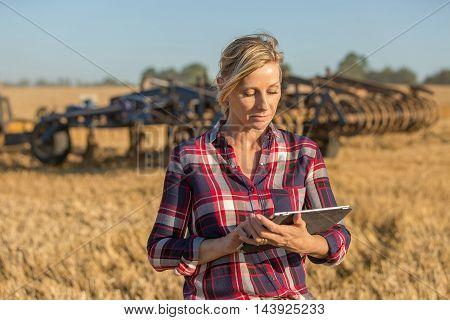portrait of female farmer standing in wheat field