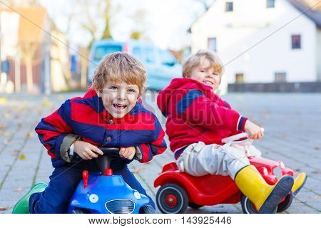 Two little kids boys in colorful clothes and rain boots driving toy cars. Siblings making competition, outdoors. Active leisure for children on autumn day