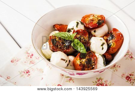Salad of roasted cherry tomatoes with mozzarella and basil sauce. Selective focus