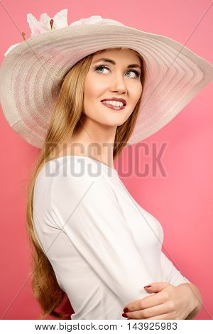 Portrait of a beautiful smiling woman in elegant hat over pink background. Beauty, fashion. Summer vacation.
